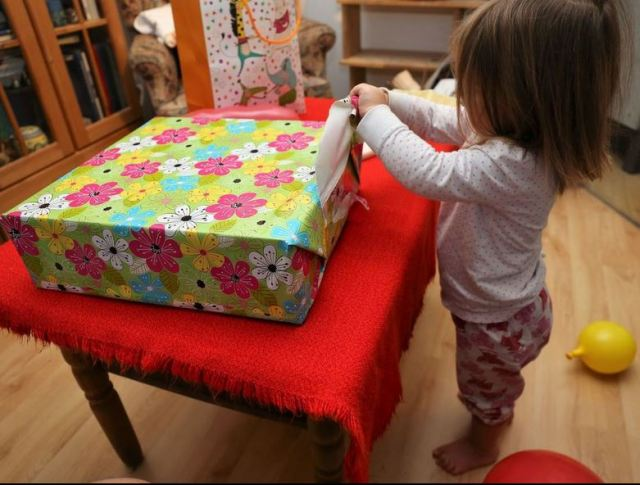 Toddler Girl unwrapping Birthday Presents